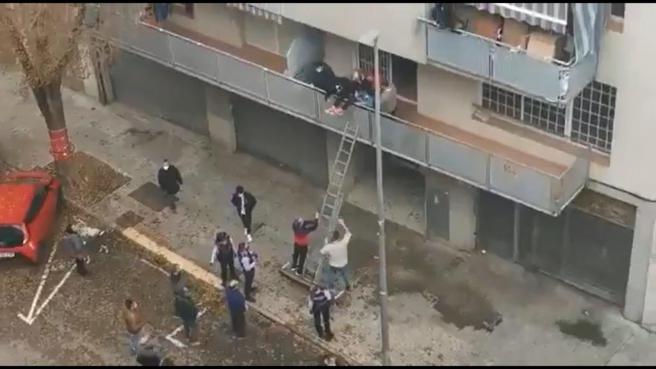 Captura del vídeo en el que vecinos de Terrassa frustran la ocupación de un piso colándose en el mismo con una escalera portátil.
