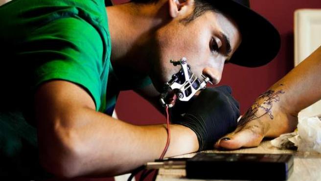Un tatuador trabajando en un pie femenino.
