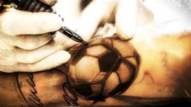 Un tatuador perfecciona un balón de fútbol.