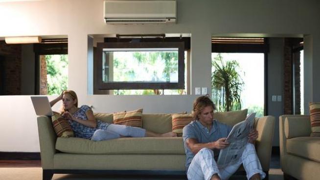Una pareja, bajo un aparato de aire acondicionado.