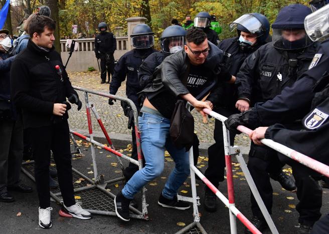 La Policía detiene a un manifestante que trataba de saltarse el cordón policial en Berlín.