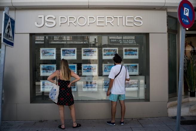 Dos personas observan propiedades en alquiler y en venta en un escaparate de una agencia inmobiliaria ubicada en Palma.