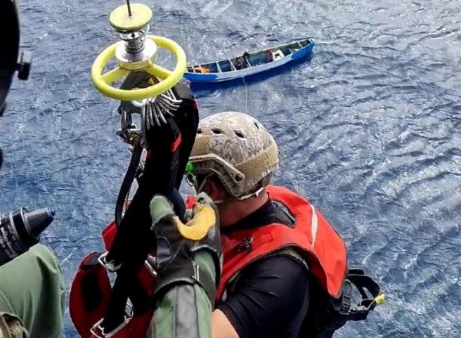 Un rescatador del Ejército del Aire se descuelga para recoger a los supervivientes de un cayuco localizado con 24 cadáveres a 490 kilómetros de la isla de El Hierro.