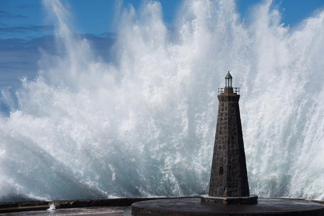 Una gran ola rompiendo contra la orilla.