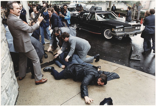 Agentes del Servicio Secreto cubren al secretario de prensa James Brady y al oficial de policía Thomas Delahanty, durante el intento de asesinato del presidente de EE UU Ronald Reagan, el 30 de marzo de 1981 en Washington DC.