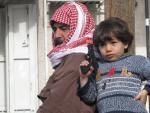 Un niño, junto a su padre, juega con una pistola de plástico en el campamento de refugiados palestinos de Kalandia.