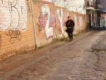 Una mujer camina por la calle Frambuesa (en el barrio madrileño de Carabanchel Alto), con el pavimento cuarteado y una acera casi inexistente.