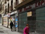 Vecinos de Carabanchel caminando frente a varios comercios cerrados en la calle General Ricardos.
