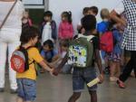 Dos niños llegan de la mano al colegio donde estudian, el Josep Maria Jujol de Barcelona, en el primer día del curso escolar en Cataluña 2014-2015.