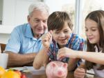 Dos niños insertan dinero en una hucha.