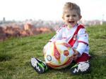 Iker, fiel hincha del Rayo, posa con su balón en el césped y con la camiseta franjirroja.