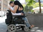 Antonio, en su silla de ruedas, sostiene sobre sus rodillas a Estel, una de las acompañantes sexuales que colabora con el colectivo Tandem Team.