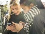 Dos adolescentes con sus teléfonos móviles.