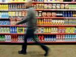 Un hombre pasea frente a una estantería en un supermercado.