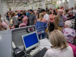 Numerosos pasajeros reclaman su vuelo, en los mostradores de facturación del aeropuerto de Palma de Mallorca, tras la quiebra de la empresa de viajes Thomas Cook.
