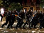 Agentes de la Policia Nacional se disponen a dispersan a los miles de personas que se han concentrado ante la consellería de Interior en Barcelona.