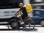 Un rider de la empresa de reparto de comida a domicilio Glovo, pasea por una calle de Madrid con su bicicleta.