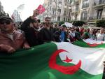 Varias personas sostienen la bandera argelina durante una protesta en la víspera de las elecciones generales.