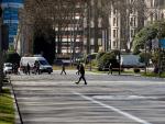 Varios viandantes cruzan Paseo de Recoletos, en el centro de la capital, prácticamente sin tráfico.