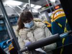 Una mujer lleva mascarilla en el autobús.