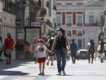 Madre e hijo pasean por Madrid con mascarilla.