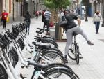 Un hombre coge una bicicleta de bicimad aparcada en una calle de la capital