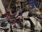 Varios vecinos intentan recuperar alguna pertenencia entre una montaña de muebles y objetos, cubiertos de lodo, tras el paso del tifón Vamco, en Marikina City (Flipinas).