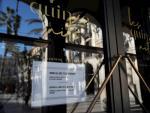 Detalle del cartel informativo colocado en la puerta de uno de los bares de la plaza Real de Barcelona que informa de su reapertura.