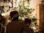 Dos personas sentadas frente al árbol de Navidad.