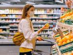 Una joven comprando fruta en un supermercado