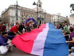 Representantes de la Federación Estatal de Lesbianas, Gays, Transexuales y Bisexuales despliegan la 'bandera bisexual' más grande de Europa, este jueves en la Puerta del Sol de Madrid.