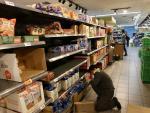 Martha, la cajera de un súper del centro de Madrid aprovecha también para reponer los productos recién llegados.
