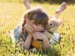 Una niña abraza su osito de peluche.