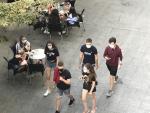 Gente paseando con mascarilla delante de una terraza