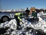 Máquinas quitanieves, efectivos de la Guardia Civil y de la UME trabajan en el km 58 de la M-40 en las inmediaciones del acceso M607 para liberar de la nieve a varios coches. Los vehículos quedaron varados en la carretera el pasado vierne