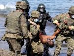 Cuatro miembros del Ejército de Tierra trasladan a un migrante que ha cruzado los espigones fronterizos.