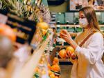 Mujer joven comprando en el supermercado con mascarilla