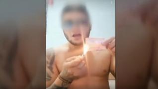 El detenido quemando billetes.