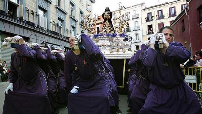 """En Madrid, Jesús Nazareno. Los 42 porteadores del paso de Jesús Nazareno """"El Pobre"""", a punto de realizar una parada durante la procesión que recorre parte del centro de Madrid en Jueves Santo."""