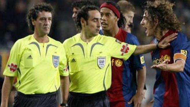 Iturralde González, en el centro, aparta a Rafa Guerrero (derecha) de los jugadores del Barça (Guido Manuilo/EFE).