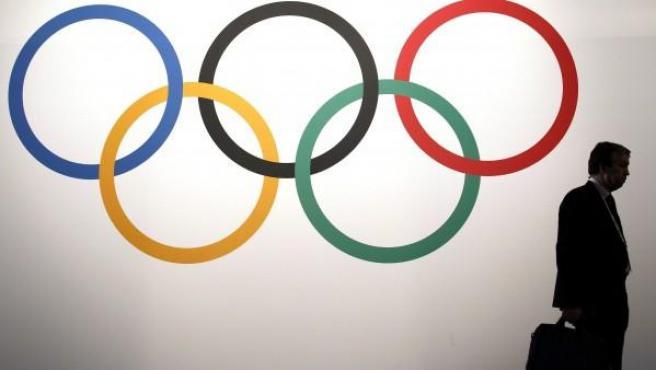Un delegado pasa por delante de los anillos olímpicos antes de la inauguración del 127 Sesión del COI, en Mónaco, el lunes 8 de diciembre de 2014.