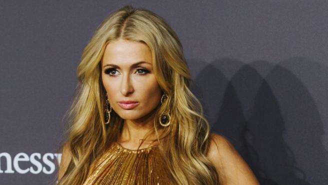 La celebridad estadounidense Paris Hilton, con un modelo en tonos dorados, posa en el photocall de la Gala amfAR New York 2017.