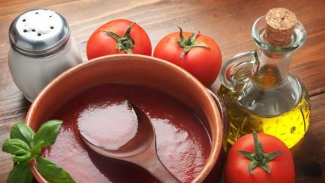 Imagen de un salero junto a una salsa de tomate.