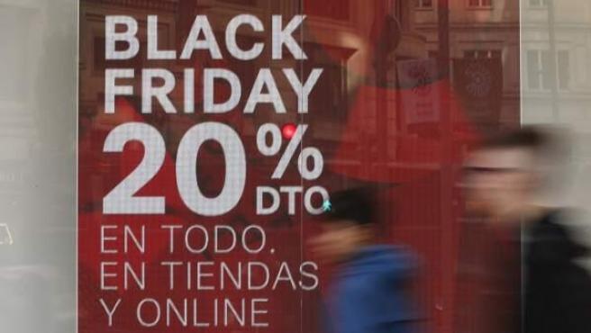 Varias personas pasan delante de una tienda en Madrid en la jornada de Black Friday.