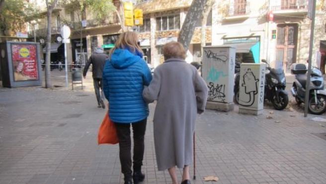 Imagen de archivo de una anciana con dependencia acompañada de una cuidadora.