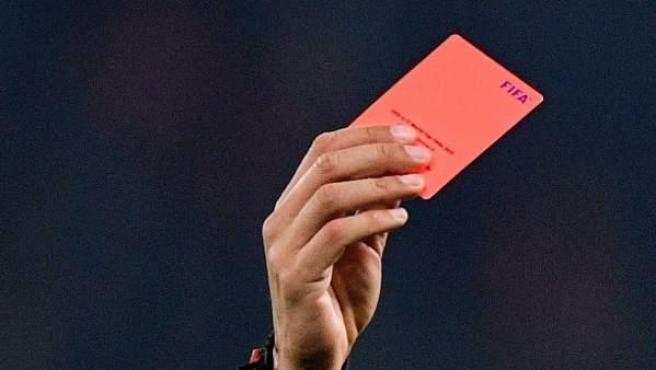 Un árbitro saca una tarjeta roja.