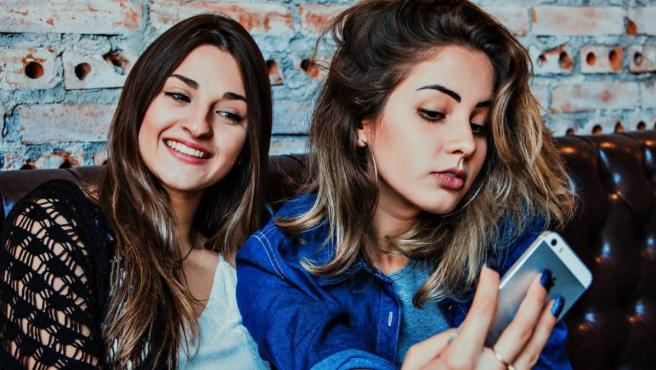 Dos chicas se hacen un 'selfie' con el teléfono móvil.