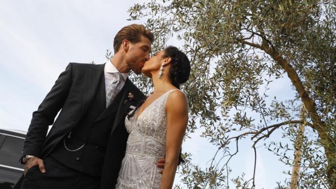 La presentadora Pilar Rubio y el futbolista Sergio Ramos se besan poco antes de entrar en la fiesta de celebración de su boda.