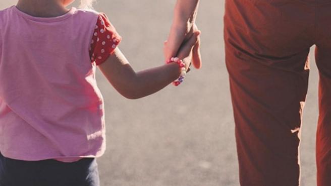 Un padre y una madre con su hija de la mano.