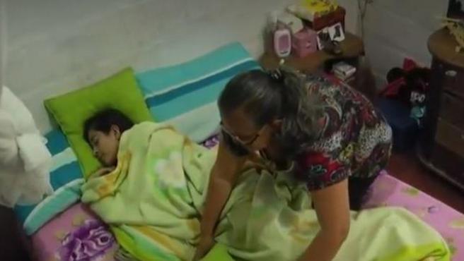 Marleny Tovar acomoda a su hija Sharik mientras duerme.